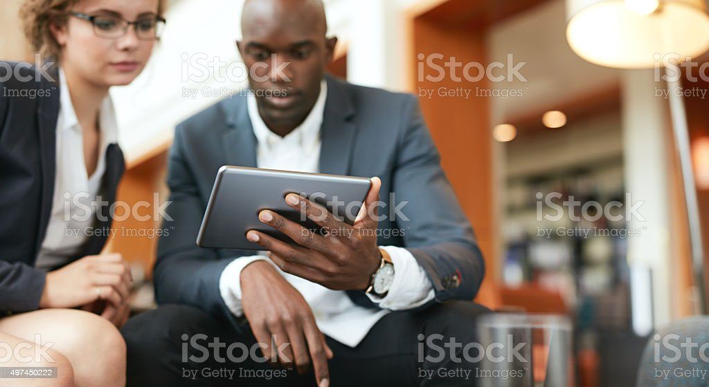 Businesspeople sitting together using digital tablet stock photo