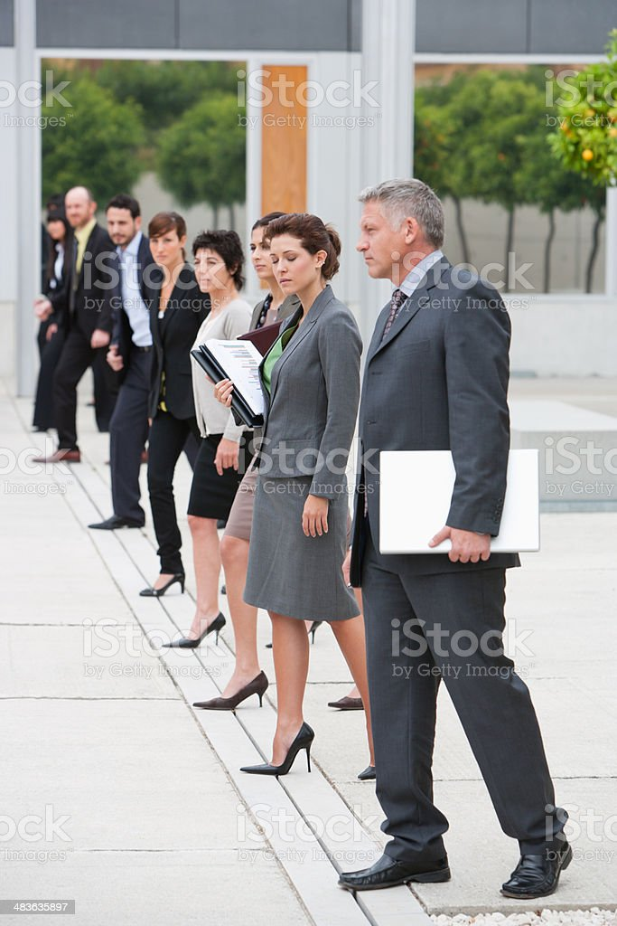 Businesspeople standing in office building courtyard stock photo