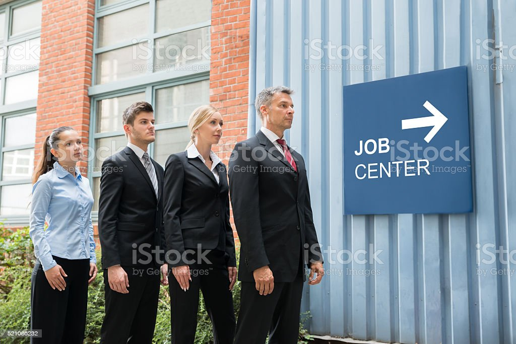 Businesspeople Standing Near The Job Center Signboard stock photo