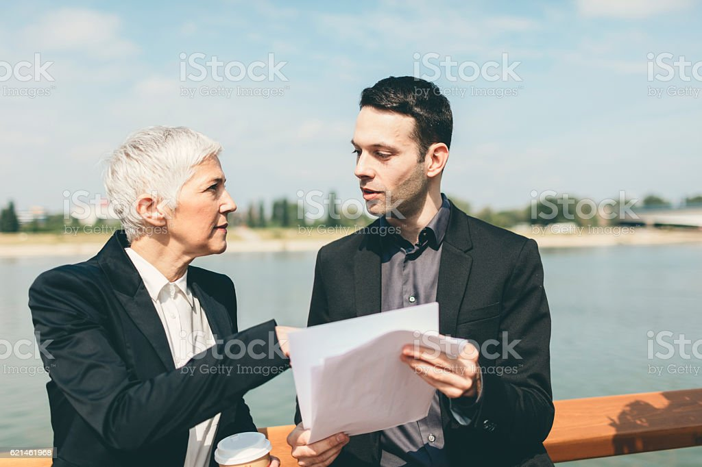 Businesspeople Standing On The Waterfront And Examining Documents. stock photo