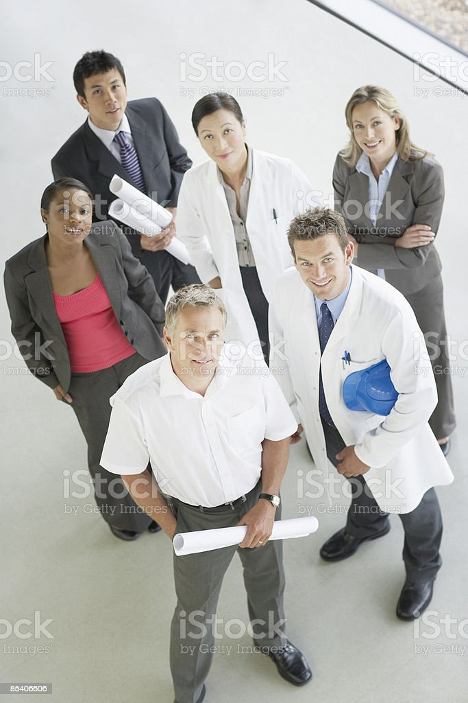 Businesspeople standing with blueprints royalty-free stock photo