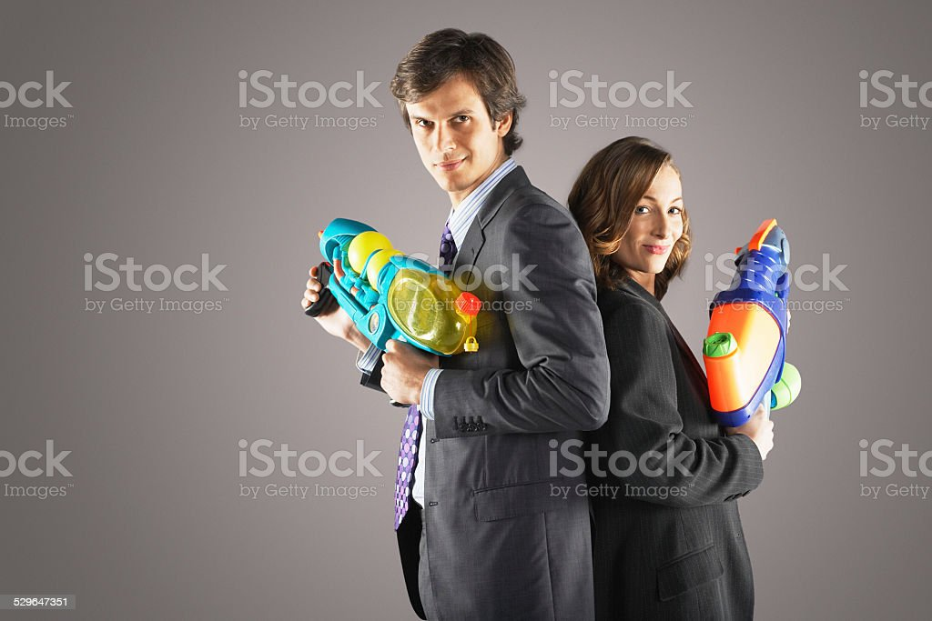 Businesspeople Standing With Water Guns stock photo