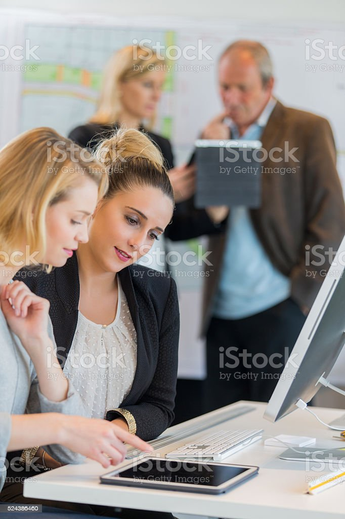 Businesspeople using laptop at conference table stock photo