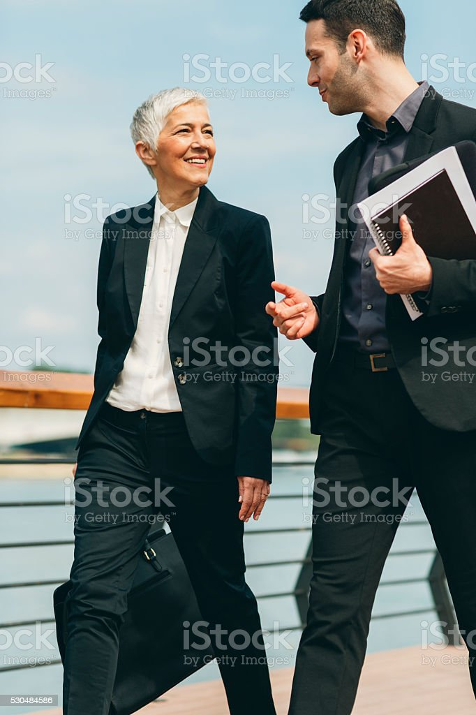 Businesspeople Walking and Talking outdoors. stock photo