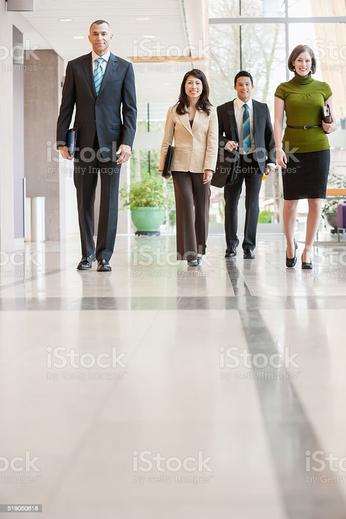 Businesspeople walking down a hallway stock photo