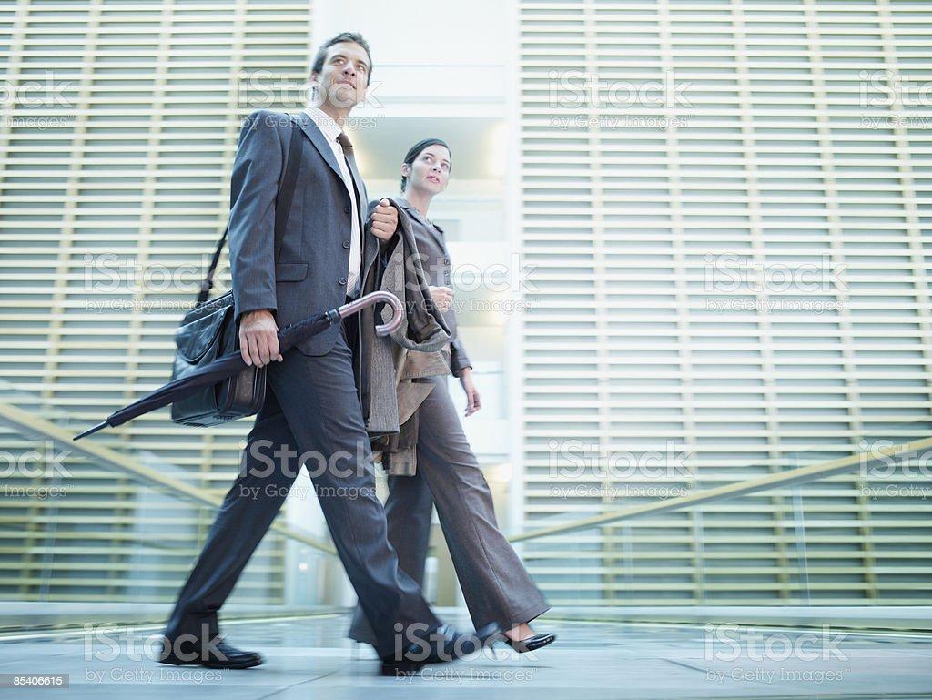Businesspeople walking in building atrium stock photo