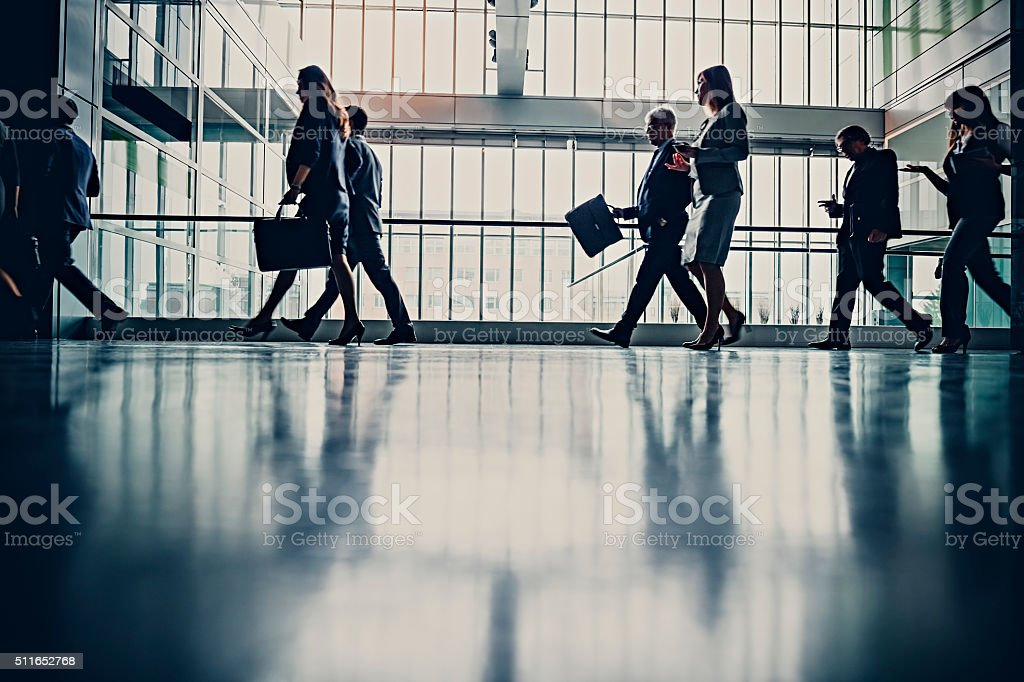 Businesspeople walking in busy office building stock photo