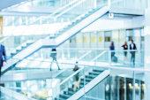 Businesspeople walking in office corridor, defocused
