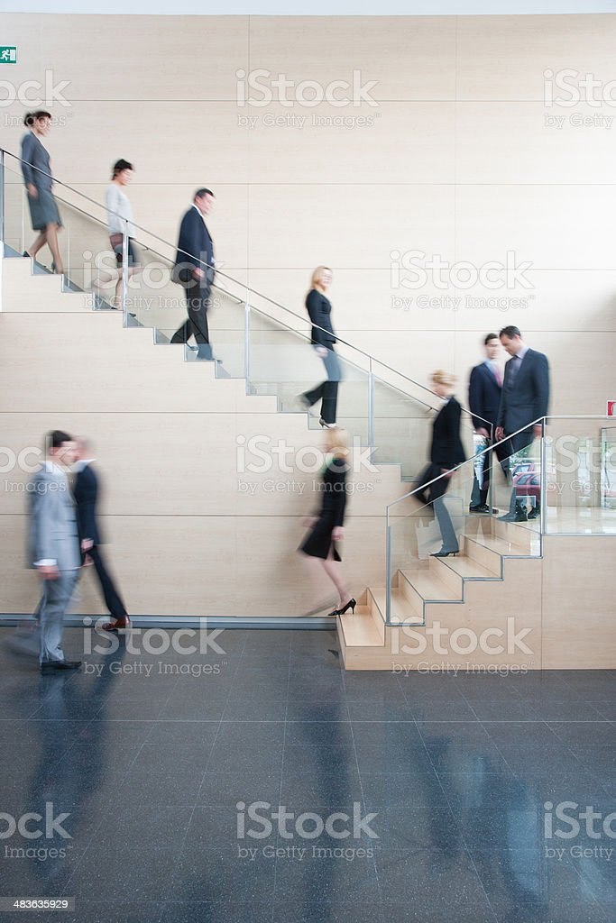 Businesspeople walking on office staircase stock photo