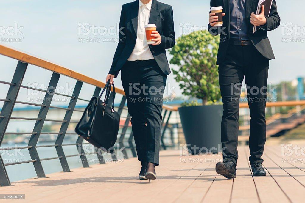Businesspeople walking outdoors. stock photo