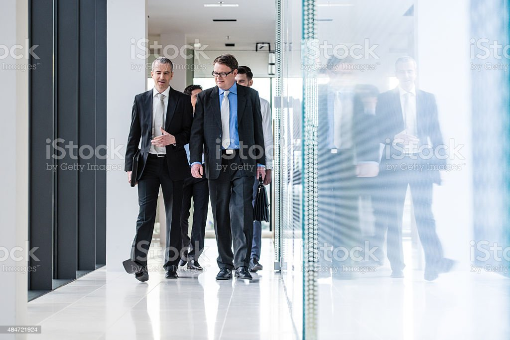 Businesspeople walking through office corridor stock photo