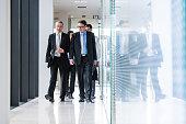 Businesspeople walking through office corridor