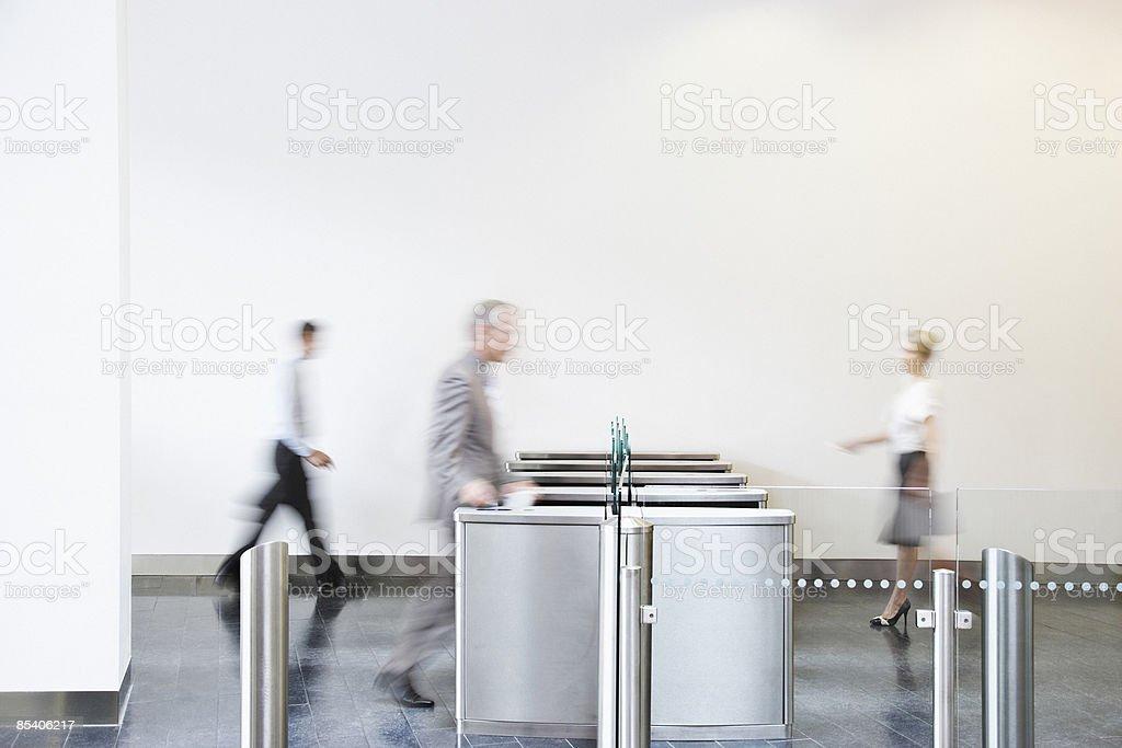 Businesspeople walking through turnstile stock photo