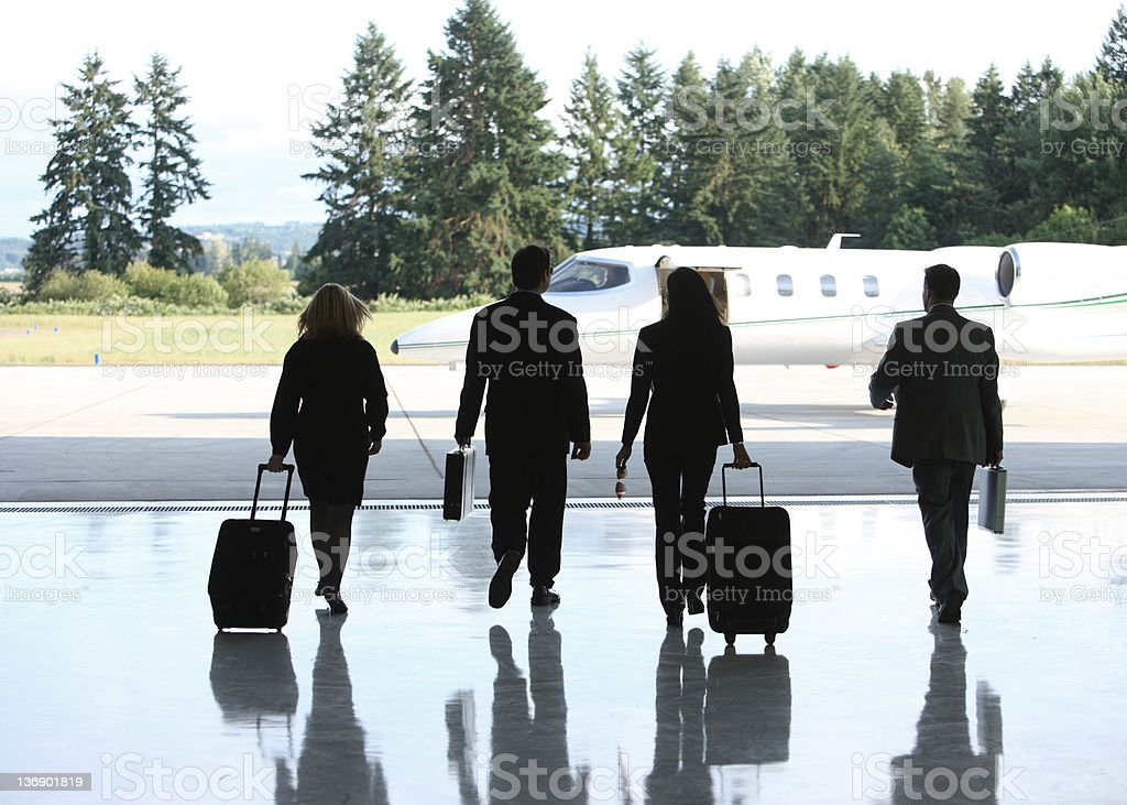 Businesspeople walking to corporate jet with suitcases stock photo