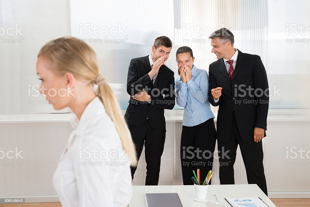 Businesspeople Whispering About Woman stock photo