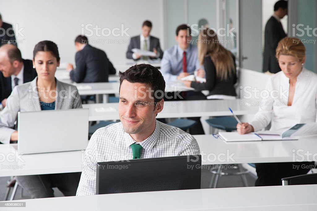 Businesspeople working in corporate training facility stock photo
