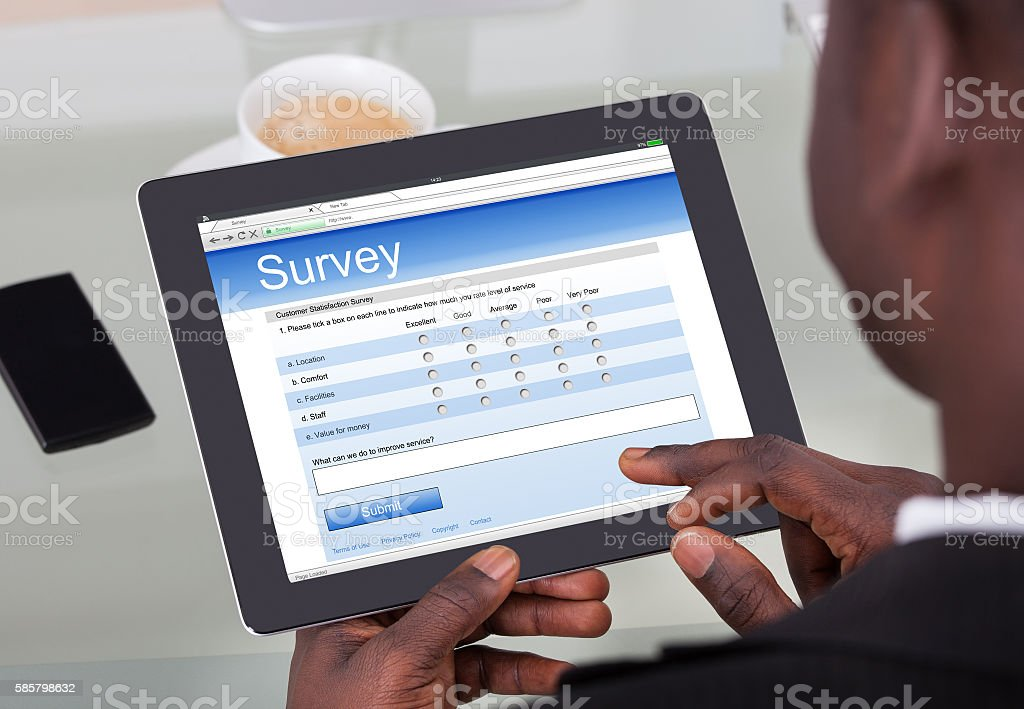 Businessperson Filling Survey Form On Digital Tablet stock photo