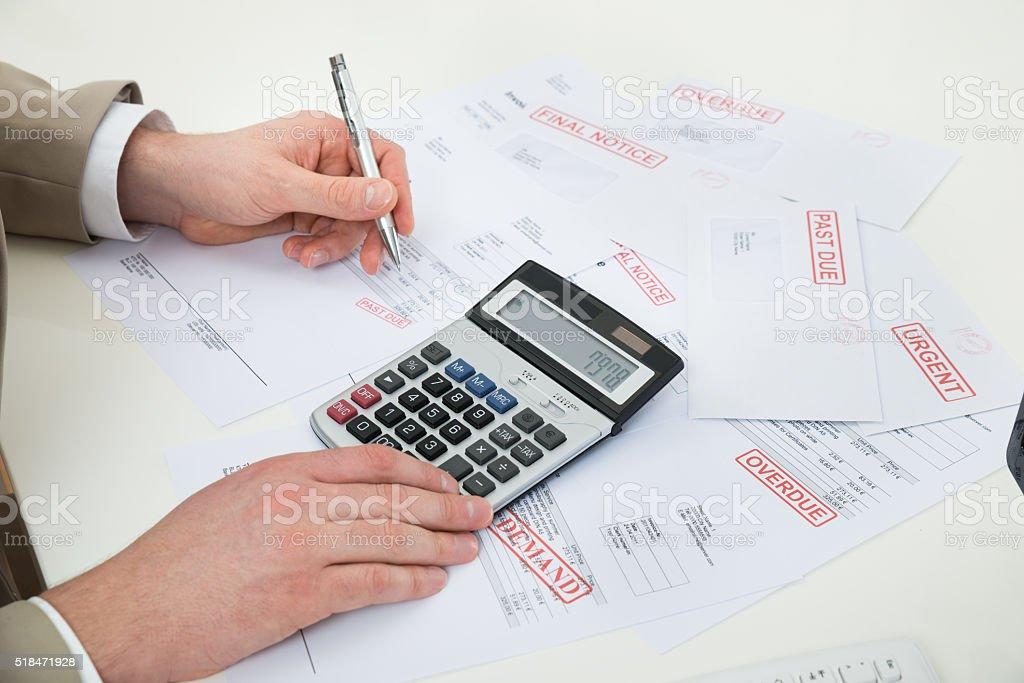 Businessperson Hand Calculating Bills stock photo