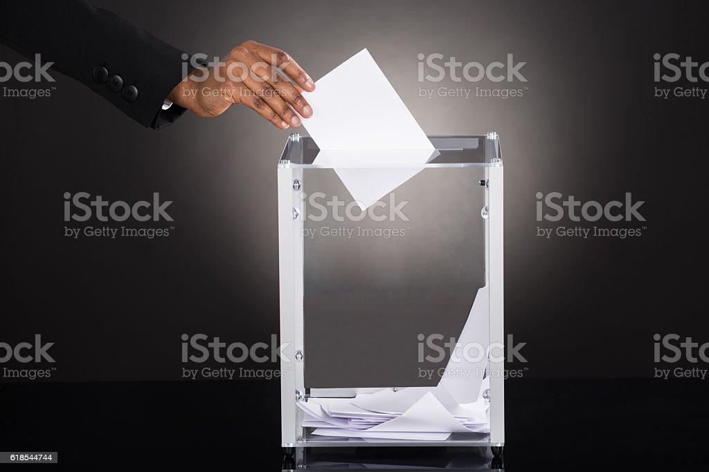 Businessperson Hand Inserting Ballot In Box stock photo