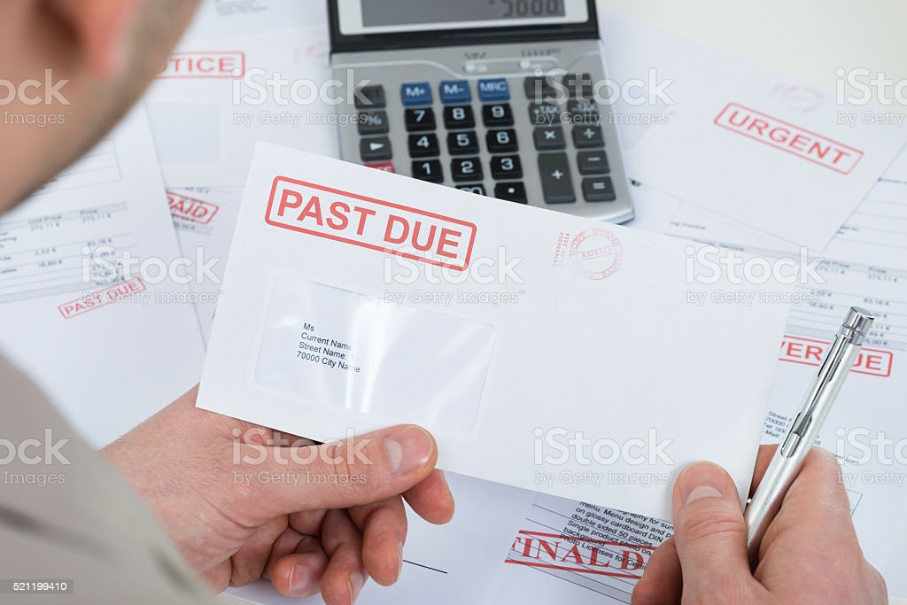 Businessperson Hand With Past Due Envelope stock photo