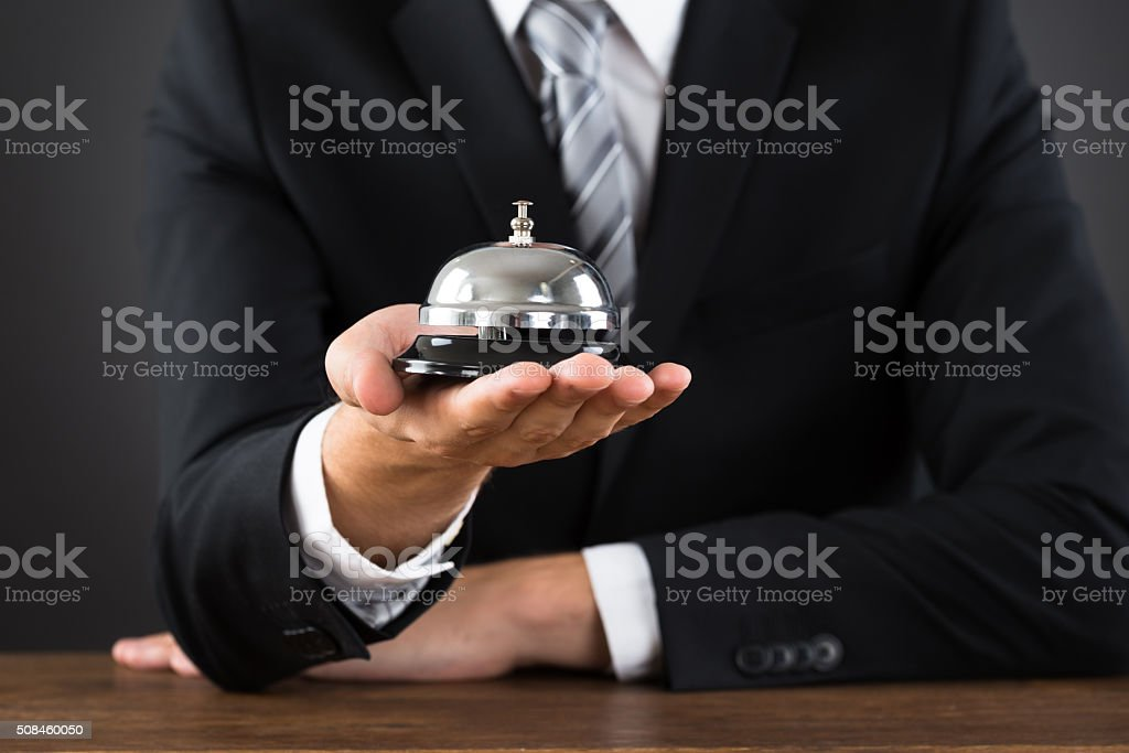 Businessperson Hands Holding Service Bell stock photo