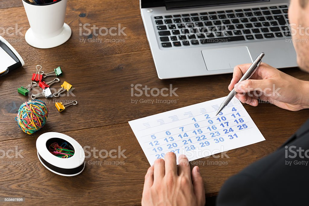 Businessperson Holding Pen Over Calendar stock photo