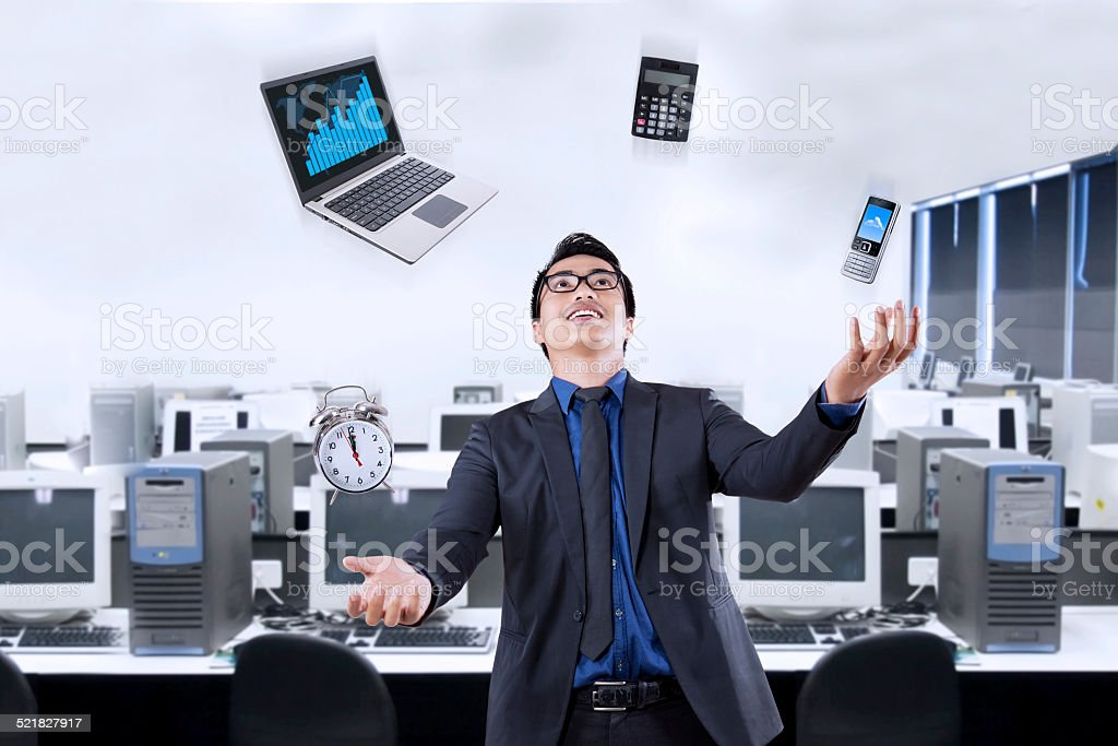 Businessperson juggling with business items stock photo