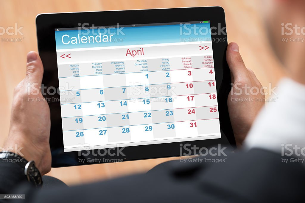 Businessperson Looking At Calendar On Digital Tablet stock photo