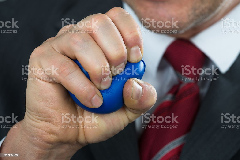 Businessperson Pressing Stressball In Hand stock photo