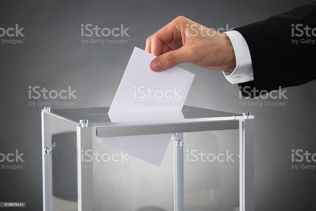 Businessperson Putting Ballot In Box stock photo