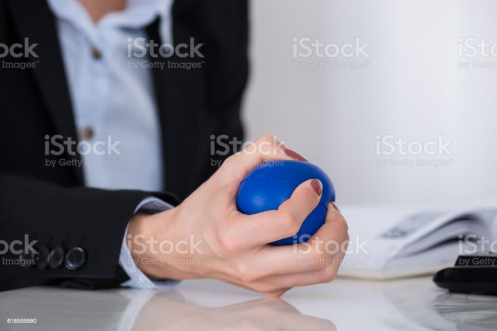 Businessperson Squeezing Stressball In Hand stock photo