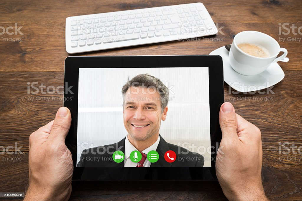 Businessperson Video Chatting With Colleague stock photo