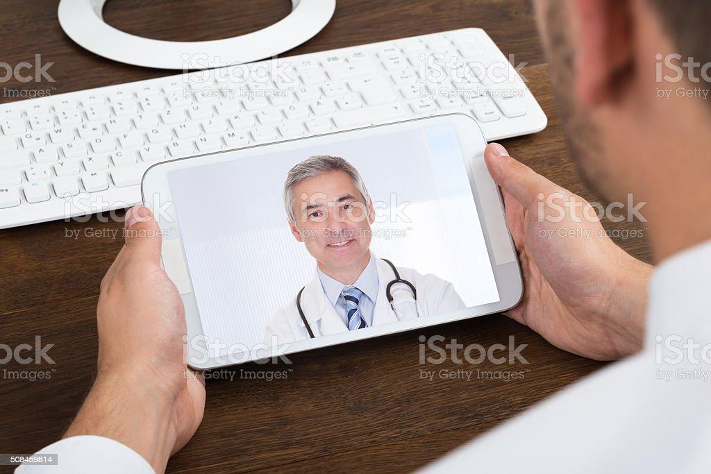 Businessperson Videochatting With Senior Doctor stock photo