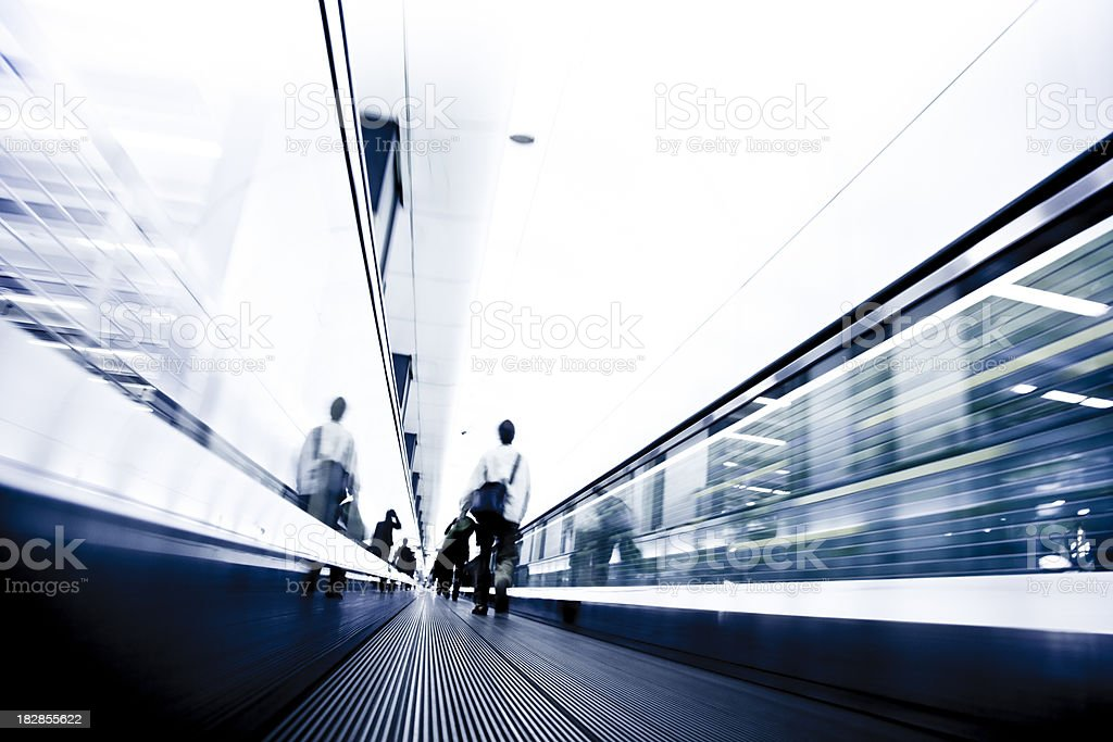 businessperson walking on a moving stairway in tokyo, japan. royalty-free stock photo