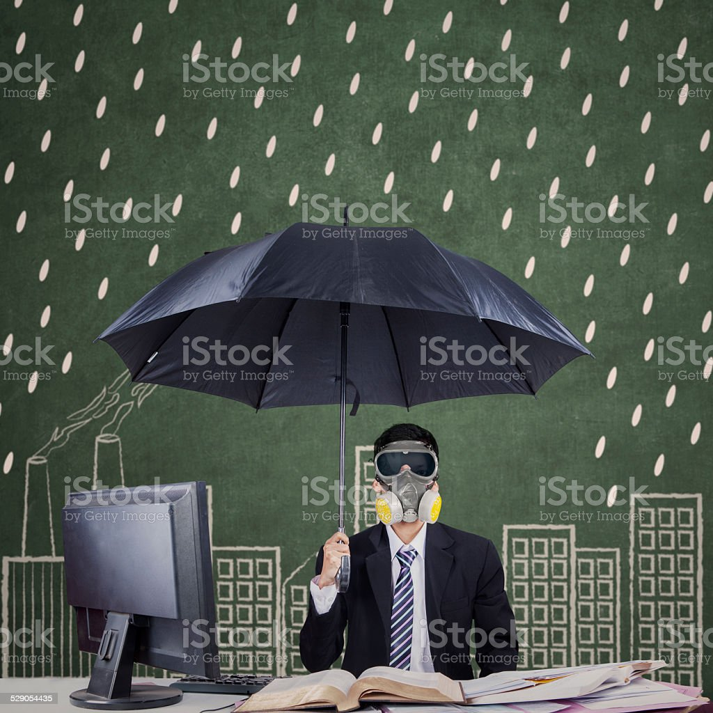 Businessperson with umbrella and mask stock photo