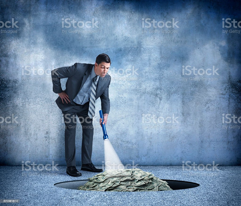 BusinessUse Flashlight To Find Pile Of Money In Hole stock photo