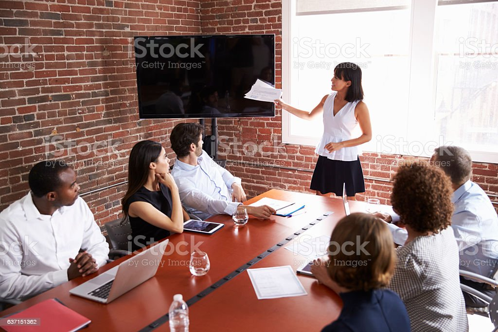 Businesswoman Addressing Boardroom Meeting With Screen stock photo