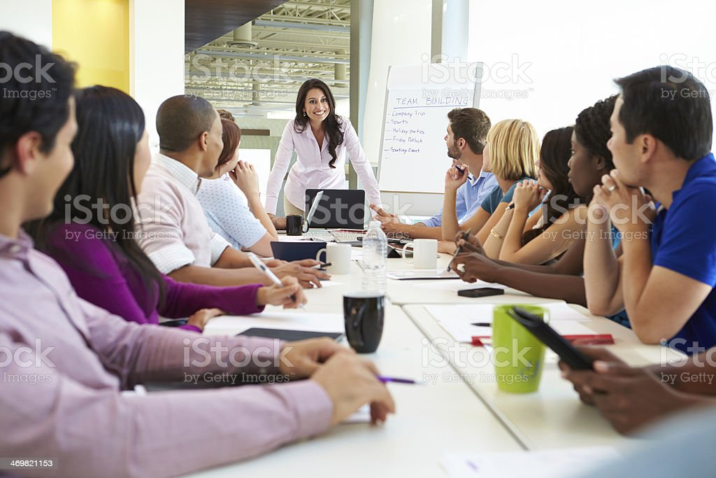 Businesswoman Addressing Meeting Around Boardroom Table stock photo