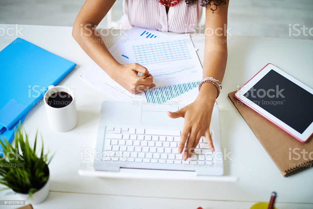 Businesswoman analyzing financial statistics sitting at office desk stock photo