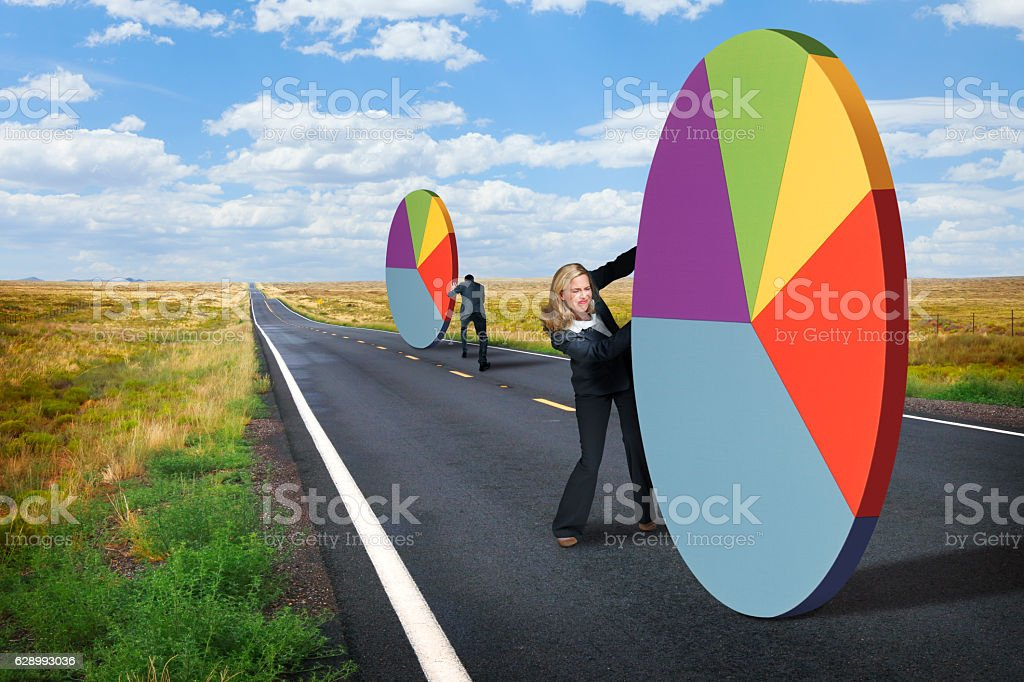 Businesswoman And A Businessman Push Pie Charts On Highway stock photo