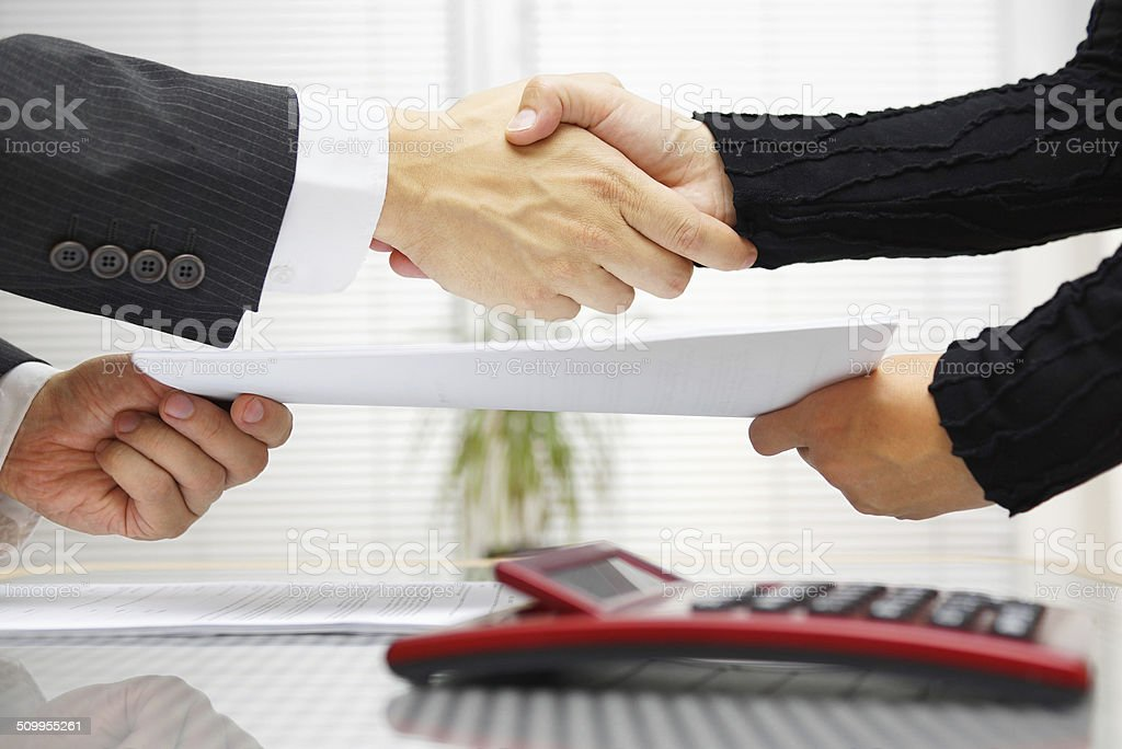 businesswoman and businessman are handshaking and exchanging contract documents stock photo