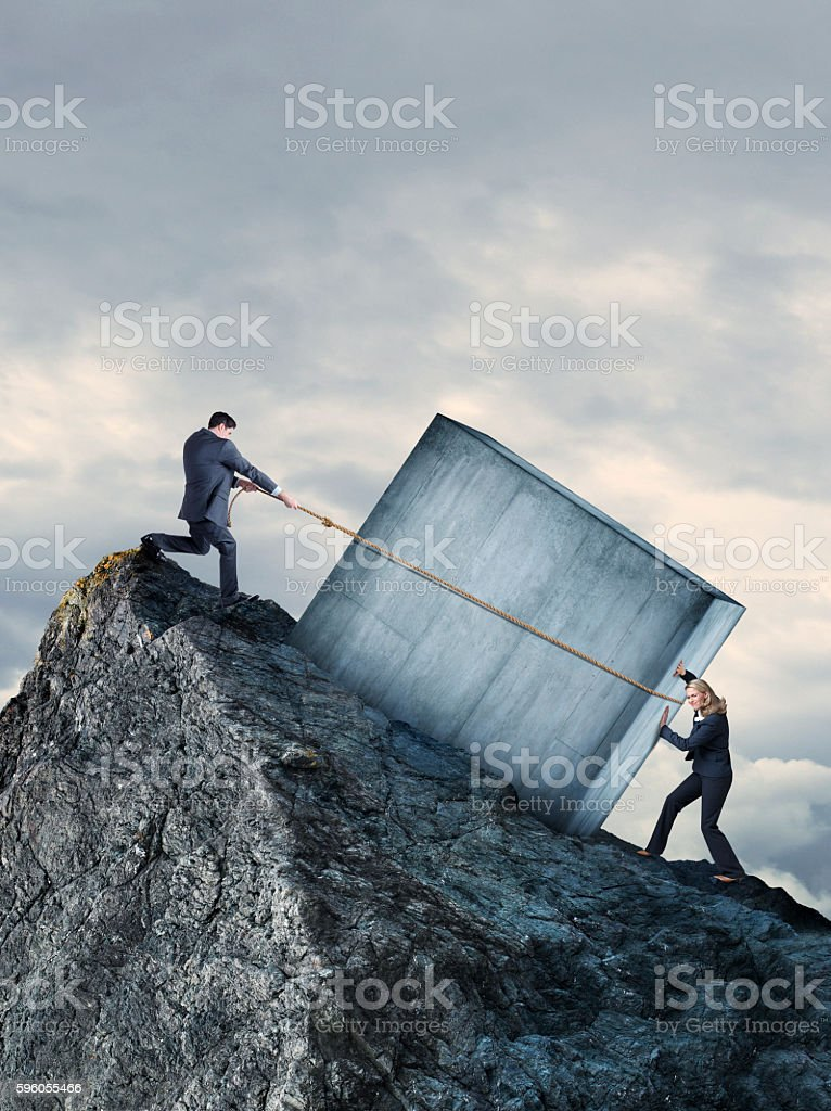 Businesswoman And Businessman Attempting To Move Concrete Uphill stock photo