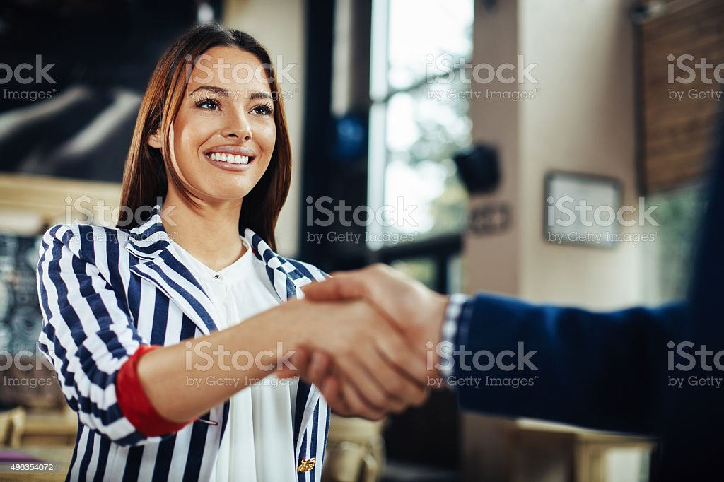Businesswoman and businessman handshake in the cafe stock photo