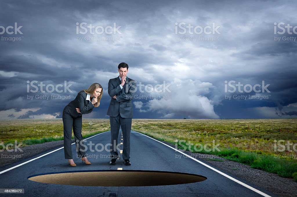 Businesswoman And Businessman Look Into Hole In Middle Of Road stock photo
