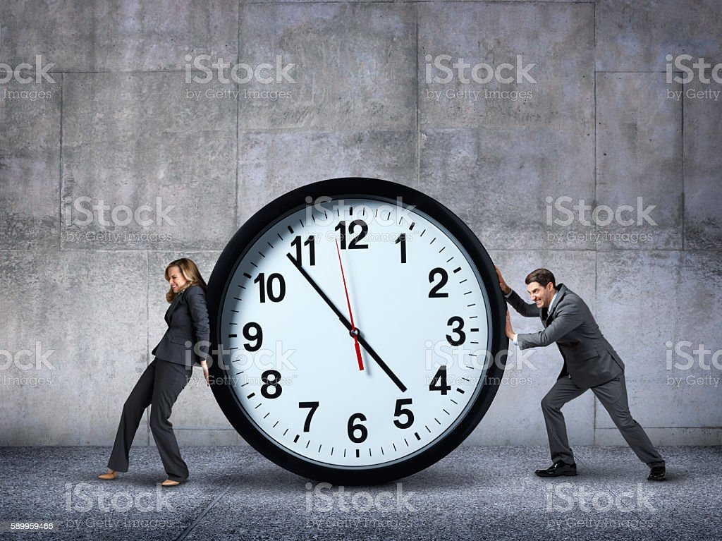 Businesswoman And Businessman Pushing In Opposite Directions Against A Clock stock photo