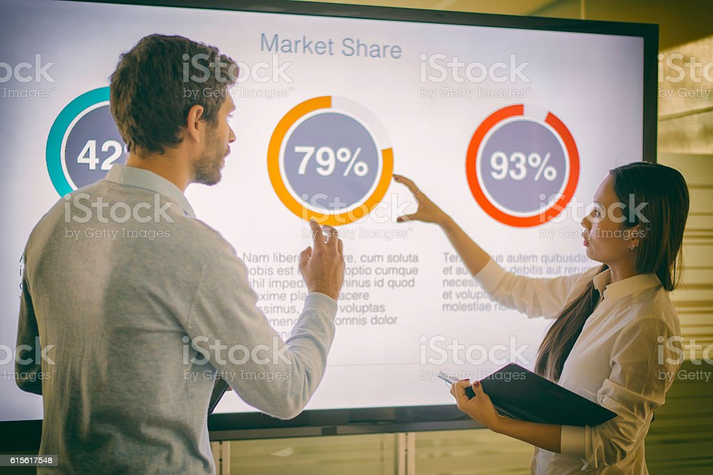 Businesswoman and businessman talking about market share stock photo