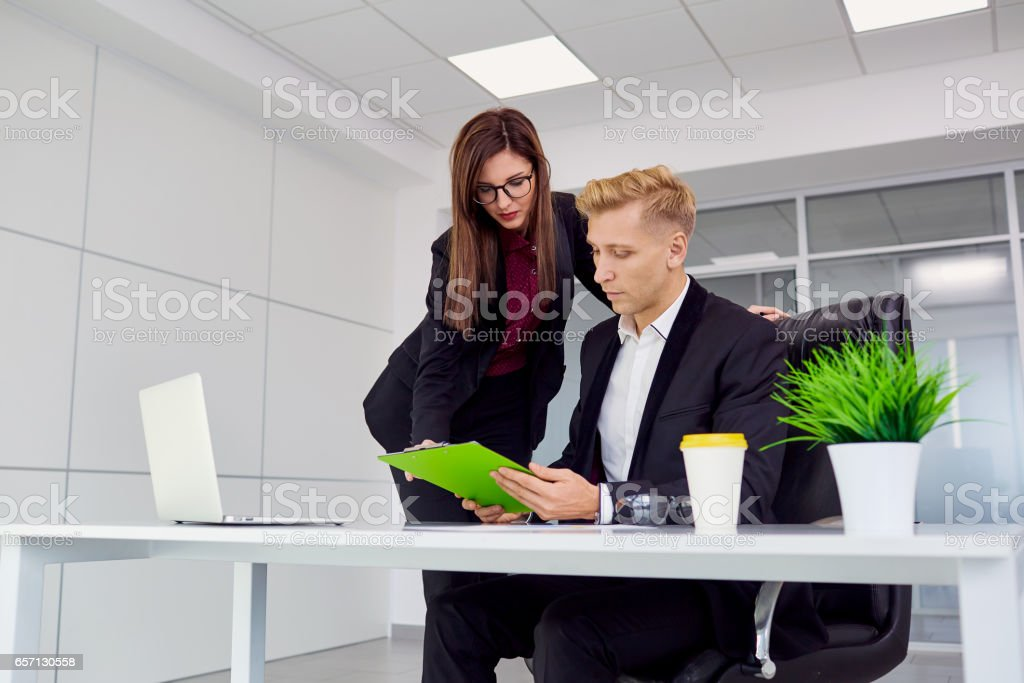 Businesswoman and businessman working at his desk in the office stock photo