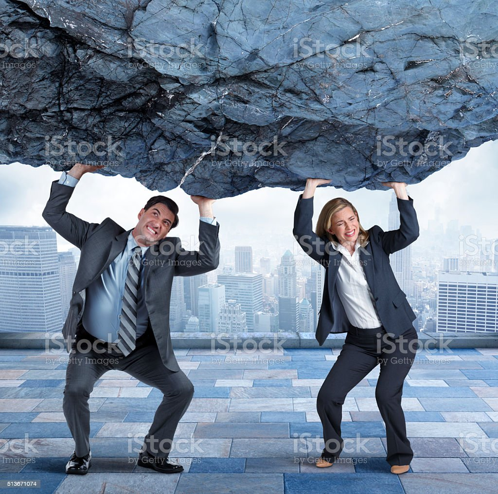 Businesswoman And Businesswoman Lifting Large Boulder In Urban Scene stock photo