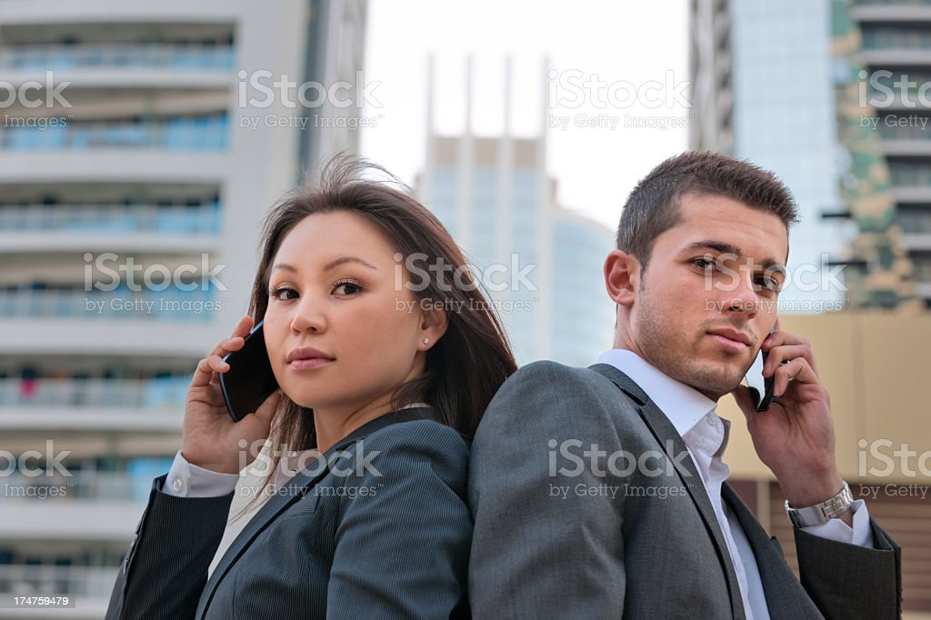businesswoman and man on the phone in Dubai royalty-free stock photo