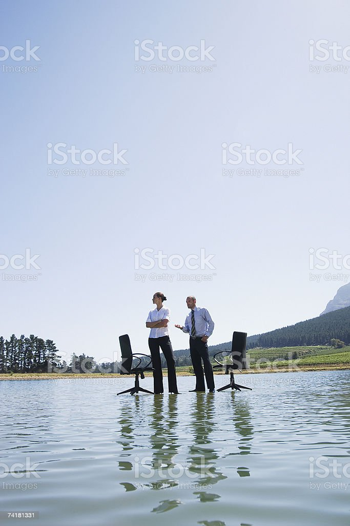 Businesswoman and man standing on water with office chairs royalty-free stock photo